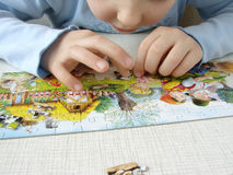 Puzzle assembling 1. Child hands assembling puzzle picture Royalty Free Stock Images