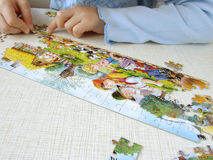 Puzzle assembling 4. Child hands assembling puzzle picture Royalty Free Stock Photo