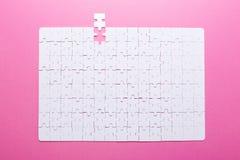 Puzzle blanc sur le fond rose Vue supérieure photo stock