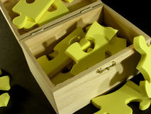Puzzle in box. The parts of yellow puzzle in the wooden box Stock Photography