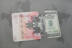 puzzle with the british pound and dollar banknote on a world map background. Royalty Free Stock Photo