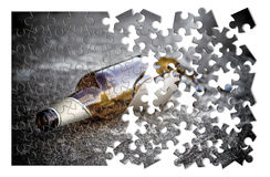 Puzzle of a broken bottle of beer resting on the ground Royalty Free Stock Images
