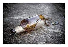 Puzzle of a broken bottle of beer resting on the ground Royalty Free Stock Photo