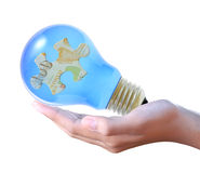 Puzzle in bulb on hand Royalty Free Stock Photos