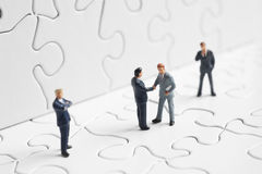 Puzzle and business figures. Business figures shaking hands on a puzzle Royalty Free Stock Image
