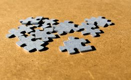 Puzzle cardboard pieces seen in perspective on a wooden brown background. Jigsaw puzzle cardboard pieces seen in perspective on a wooden brown background Royalty Free Stock Images