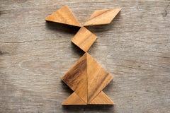 Puzzle chinois de tangram dans la forme de lapin sur l'escroquerie en bois de fond photographie stock