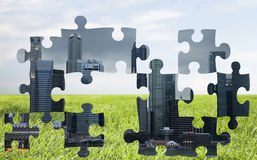 Puzzle of city over blue sky and grass background Stock Images