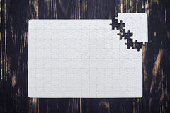 Puzzle close to soltion on dark wooden desk Royalty Free Stock Photography