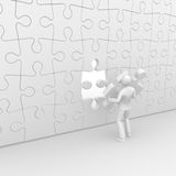 Puzzle completion. A man holding a final piece to complete a wall puzzle Royalty Free Stock Photos