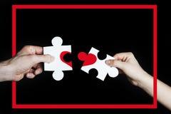 Puzzle con un cuore rosso nelle mani di una coppia amorosa nel telaio rosso Concetto di giorno del ` s del biglietto di S Cuore l fotografia stock