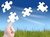 Puzzle concept. Falling puzzles. Hand holdin unique golden puzzle Royalty Free Stock Photo