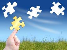 Puzzle concept. Falling puzzles. Hand holdin unique golden puzzle Stock Images