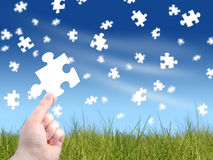 Puzzle concept. Falling puzzles on the background. Hand holding puzzle Stock Photo