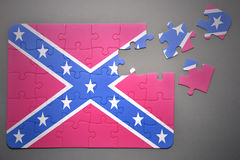 Puzzle with the confederate flag. Broken puzzle with the confederate flag on a gray background Royalty Free Stock Images