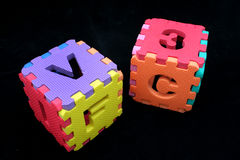 Puzzle cubes with letters. And numbers over a black background Stock Photo