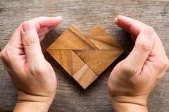 Puzzle de tangram de couverture de main dans la forme de coeur Images stock