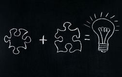 Puzzle del disegno della mano di Businessmans sulla lavagna per spiegare concetto di affari Risolvendo puzzle insieme Lampadina d fotografia stock