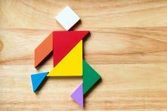Puzzle del tangram di colore nella forma corrente dell'uomo Immagini Stock