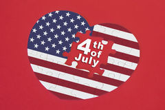 Puzzle della bandiera dell'America di forma del cuore con una parola scritta il quarto luglio Fotografia Stock