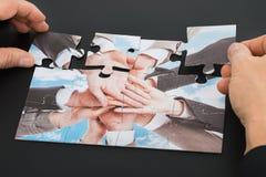 Puzzle della tenuta della mano della persona Immagini Stock