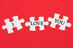 Puzzle denteux blanc avec un mot écrit je t'aime sur un fond rouge Photo stock
