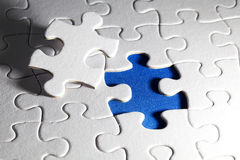 Puzzle denteux blanc simple, sur le fond bleu Images libres de droits