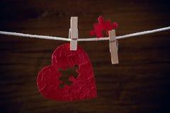 Puzzle di amore del cuore sulla corda del panno fotografia stock