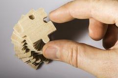 Puzzle di legno su fondo bianco. Immagine Stock