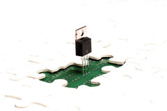 Puzzle of electronics. Microelectronics, technology, nanotechnology concept. Closeup view of circuit board with mounted microchip visible through the missing Royalty Free Stock Photos