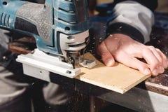 Puzzle elettrico del primo piano nelle mani di un lavoratore in un'officina domestica Iniziare un'attività artigiano immagine stock libera da diritti