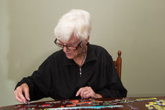Puzzle fügte durch eine eldery Frau zusammen Stockfotos