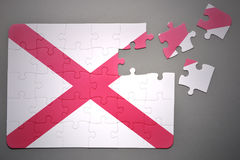 Puzzle with the flag of alabama state. Broken puzzle with the flag of alabama state on a gray background Stock Photo