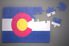 Puzzle with the flag of colorado state. Broken puzzle with the flag of colorado state on a gray background stock photo