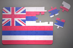 Puzzle with the flag of hawaii state. Broken puzzle with the flag of hawaii state on a gray background Royalty Free Stock Images