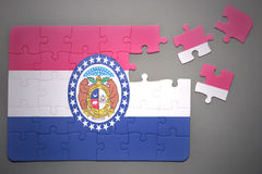 Puzzle with the flag of missouri state. Broken puzzle with the flag of missouri state on a gray background royalty free stock photos