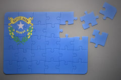 Puzzle with the flag of nevada state. Broken puzzle with the flag of nevada state on a gray background Stock Image