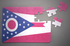 Puzzle with the flag of ohio state. Broken puzzle with the flag of ohio state on a gray background Royalty Free Stock Images