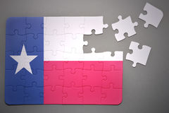 Puzzle with the flag of texas state. Broken puzzle with the flag of texas state on a gray background Stock Images