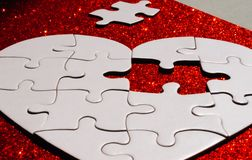Puzzle a forma di del cuore bianco su rosso fotografia stock