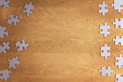 Puzzle game paper pieces pattern frame on brown wood table desk wooden background. Top view. Copy space for text Royalty Free Stock Photos