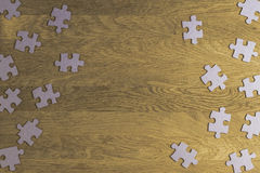 Puzzle game paper pieces pattern frame on wooden background. Top view. Copy space for text Stock Images