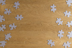 Puzzle game paper pieces pattern frame on wooden background. Top view. Copy space for text Stock Photography