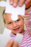 Puzzle Girl. Little girs shows solution of puzzle parts Royalty Free Stock Photos