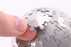 Puzzle globe. Business concept with a hand building puzzle globe on white, space for messages Stock Photo