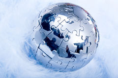 Puzzle Globe on feather. Puzzle Globe on very soft feather Royalty Free Stock Photo