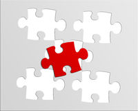 Puzzle. Gray puzzle with a red piece royalty free stock photography