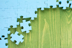 Puzzle on green wooden background Royalty Free Stock Images