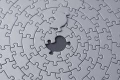 Puzzle grigio con la parte mancante che pone sopra lo spazio Fotografia Stock