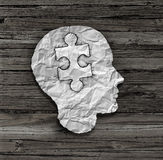 Puzzle Head Solution. Concept as a human face profile made from crumpled white paper with a jigsaw piece cut out inside the brain area on an old wood background Royalty Free Stock Image